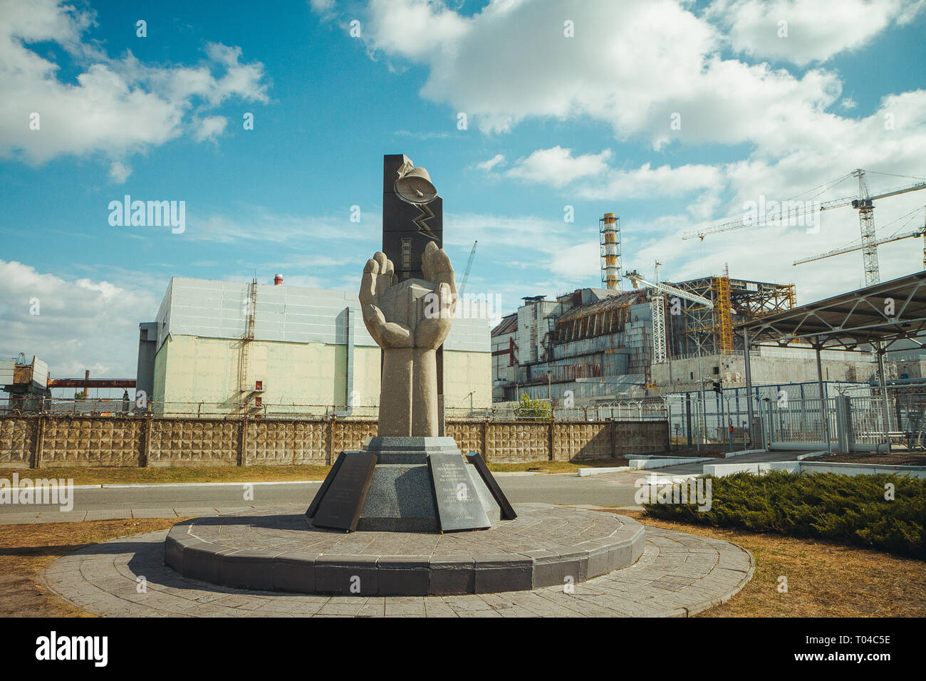 Monument to the Chernobyl Liquidators and fourth reactor without enclosing sarcophagus. Chornobyl Nuclear Power Plant - ChNPP. Radioactive zone in - Stock Image