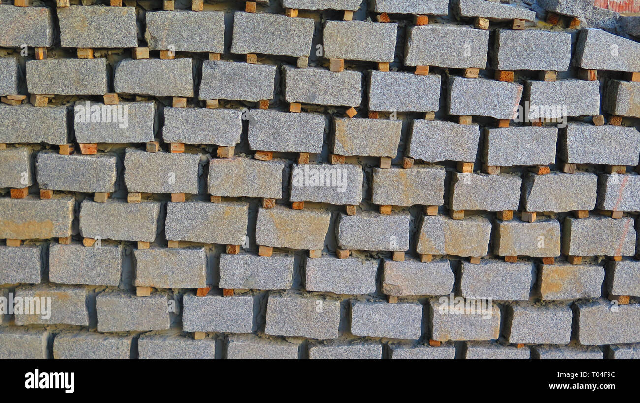 Wooden spacers between granite stone block tiling in Andalusian village - Stock Image