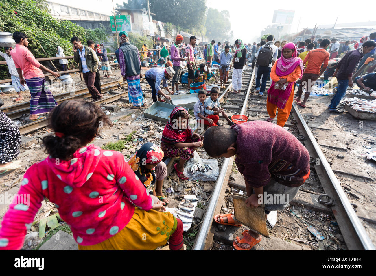 A local market set on railroad track dangerously close to passing trains, Dhaka, Bangladesh - Stock Image
