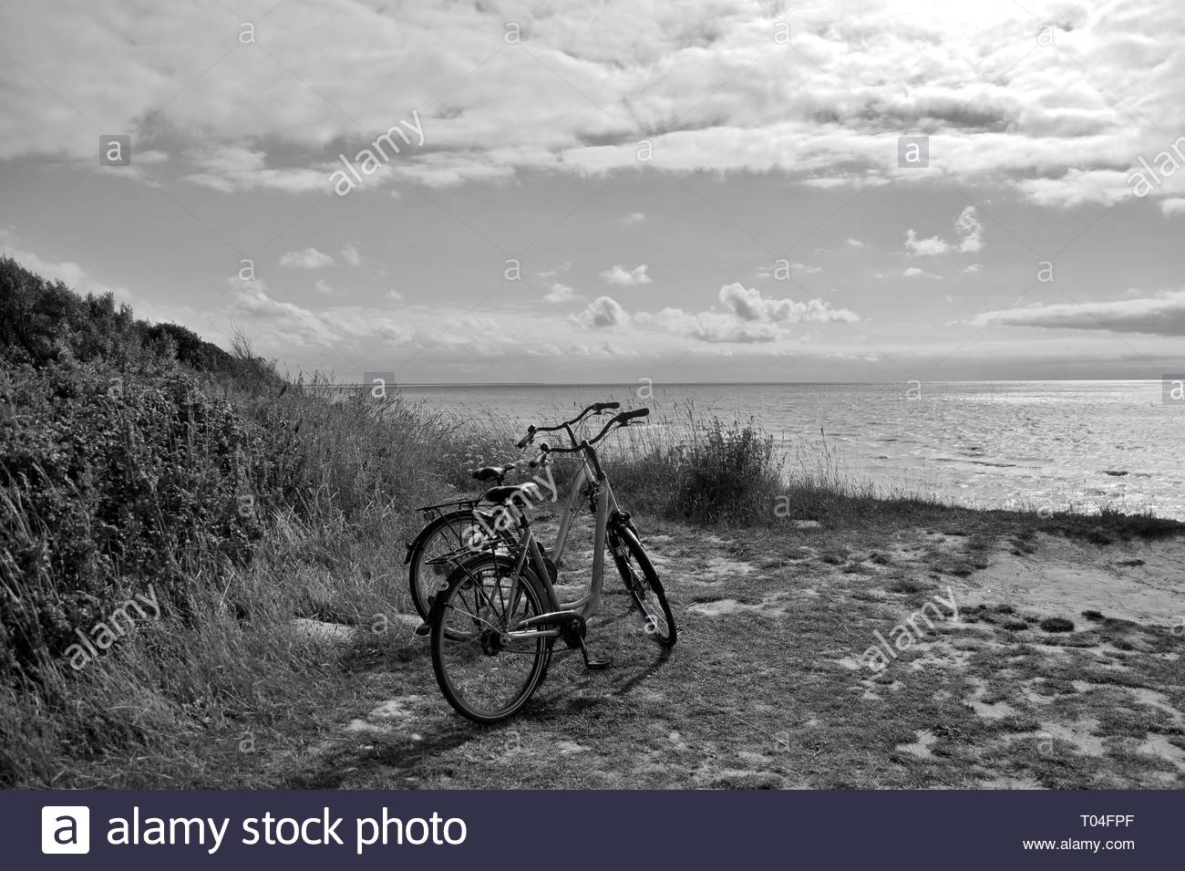 A view of two bicycles parked and a view of a beach on a sunny Day, Baltic Sea Germany, black and white Picture, - Stock Image