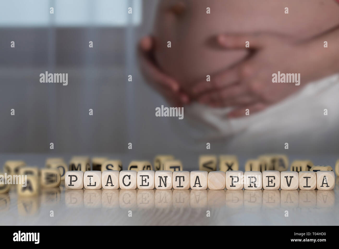 Words PLACENTA PREVIA  composed of wooden letters. Pregnant woman in the background - Stock Image