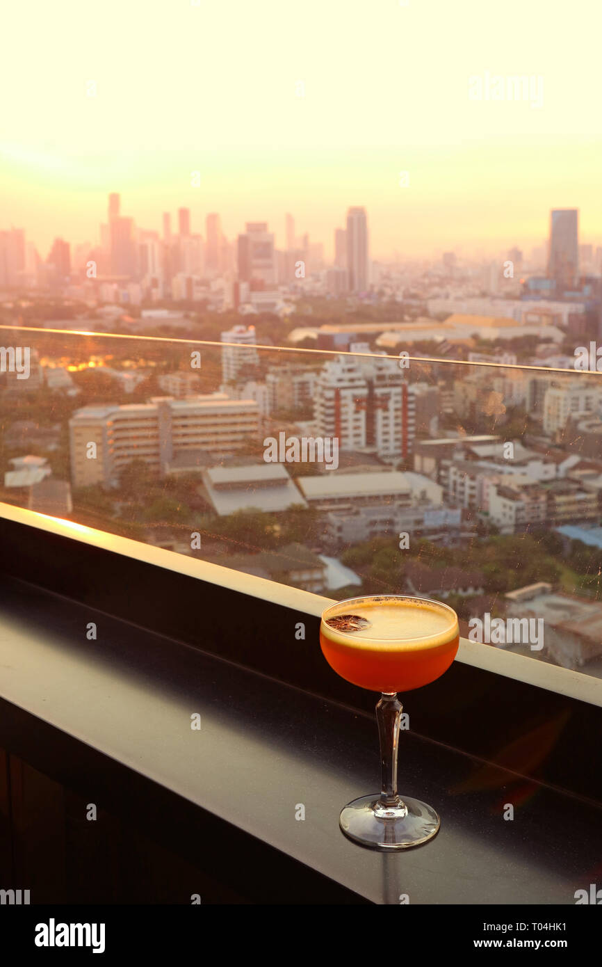 Glass of cocktail on the rooftop bar's table with aerial urban view in background - Stock Image