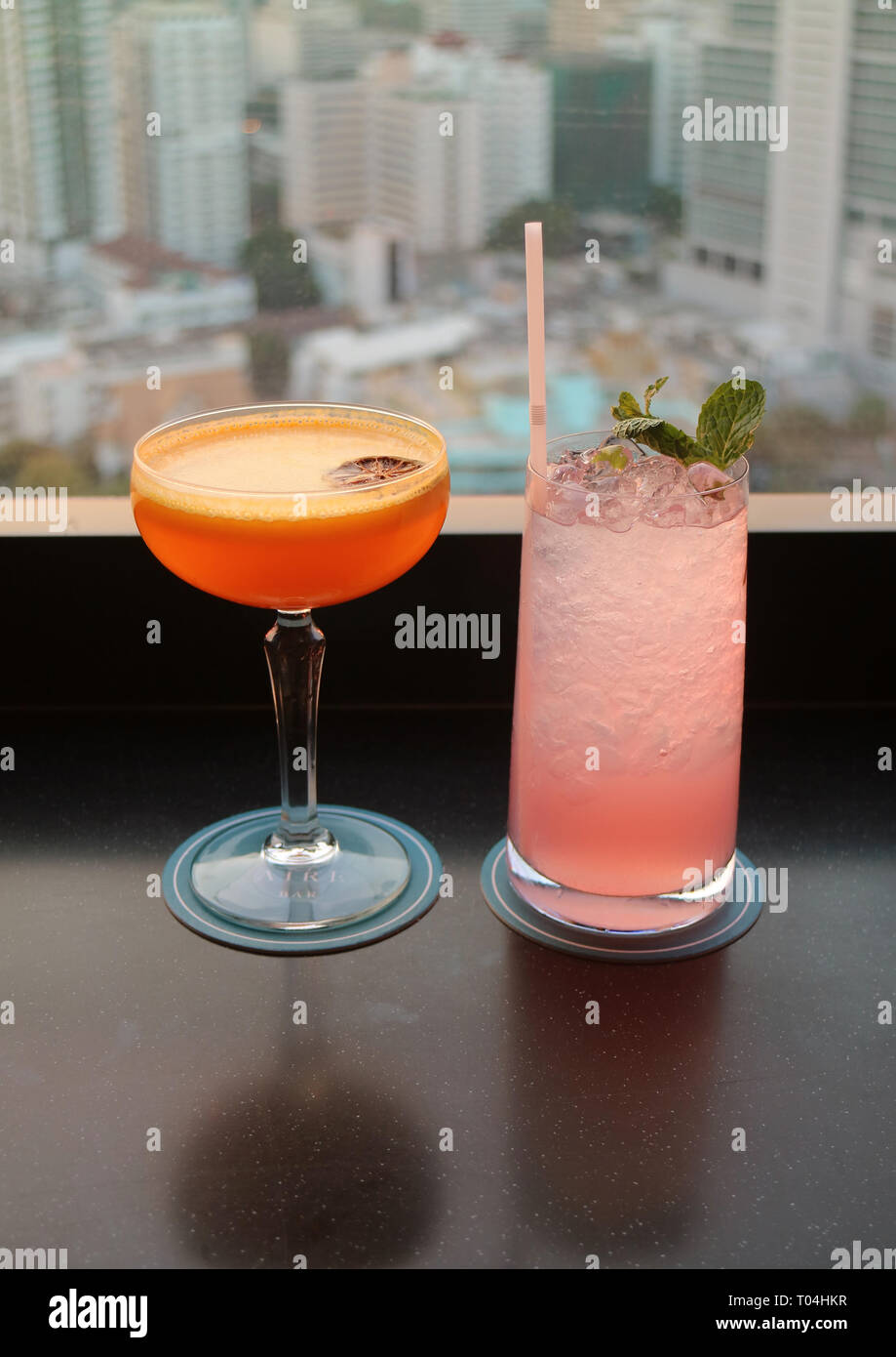 Two glasses of cocktail on the rooftop bar's table with blurry aerial urban view in background - Stock Image