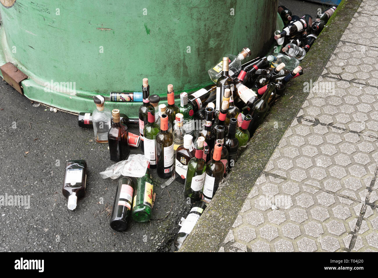 Galicia, Spain; march 8 2019: Lots of empty glass bottles near a glass container. Recycling concept - Stock Image