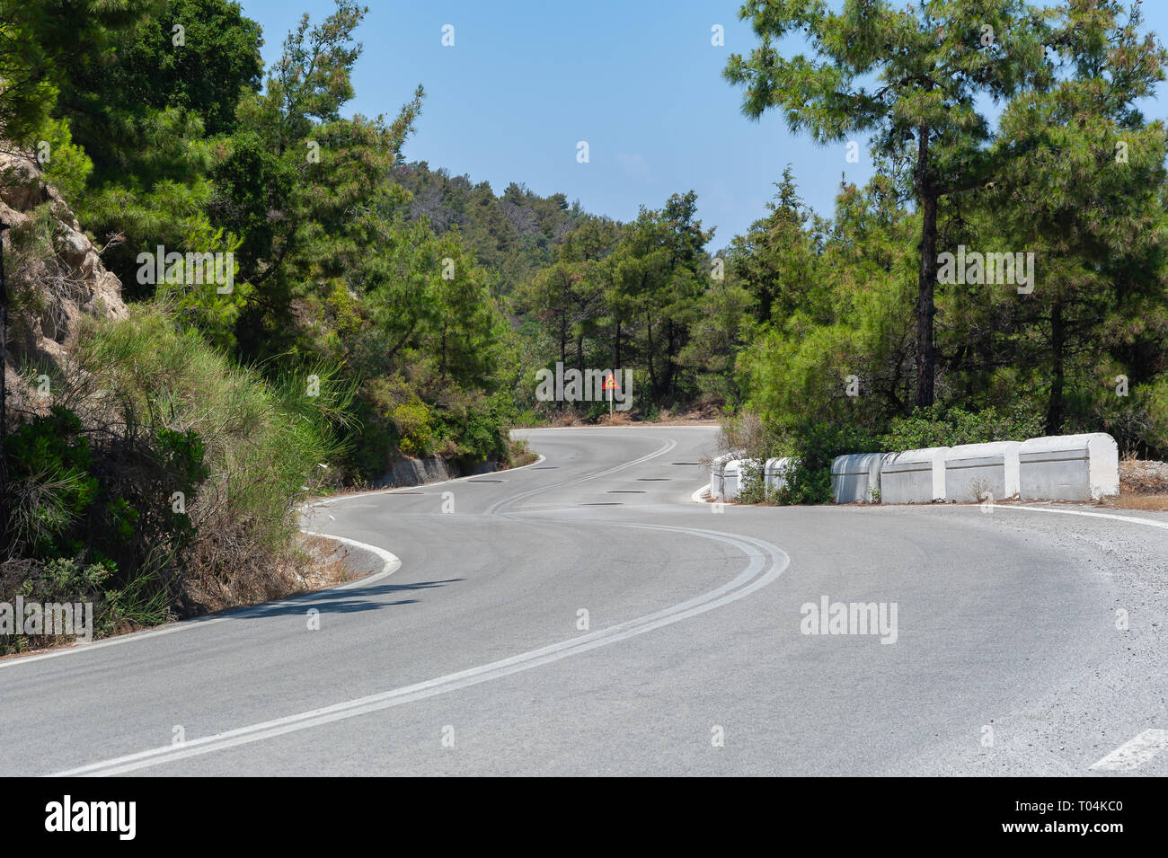 Down a curvy, bendy road. Open road through forest on hillside. Open road. Empty road with no traffic in countryside. Rural landscape. Greece. - Stock Image