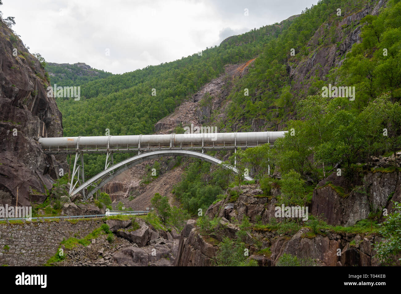 Open road in a mountain valley with a pipeline across. Empty road with no traffic in countryside. Rural landscape. Ryfylke scenic route. Norway. - Stock Image