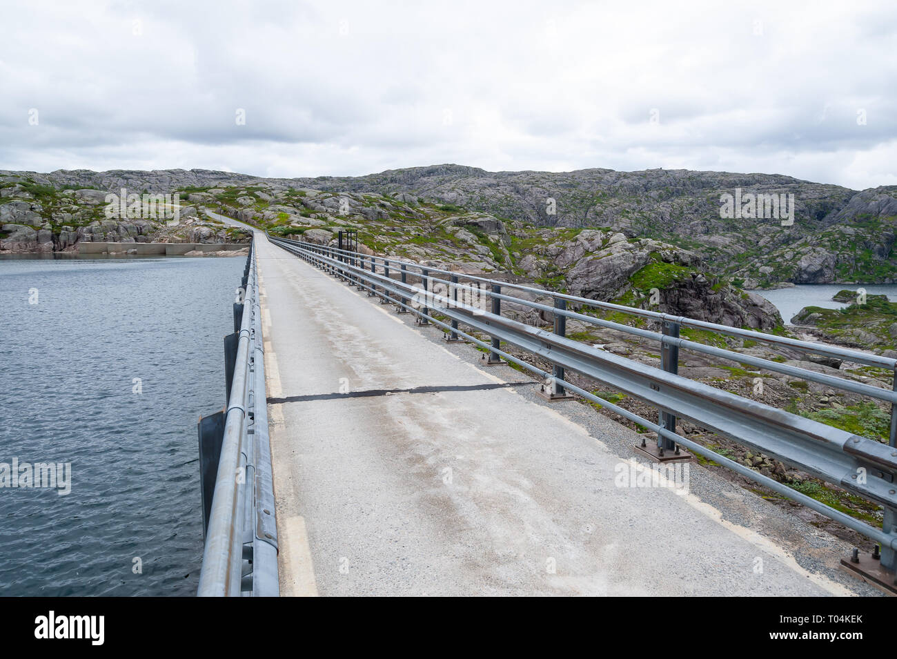 Open road on top of a small water dam. Empty road with no traffic in countryside. Rural landscape. Ryfylke scenic route. Norway. Europe. - Stock Image
