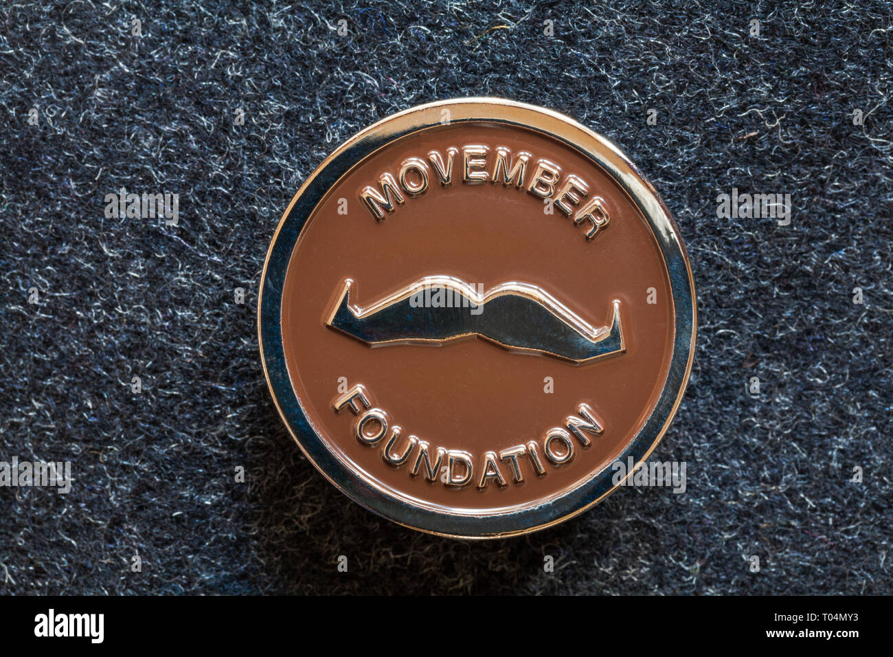 Movember pin badge from Movember Foundation helping men live happier, healthier, longer lives - Movember Foundation - Stock Image