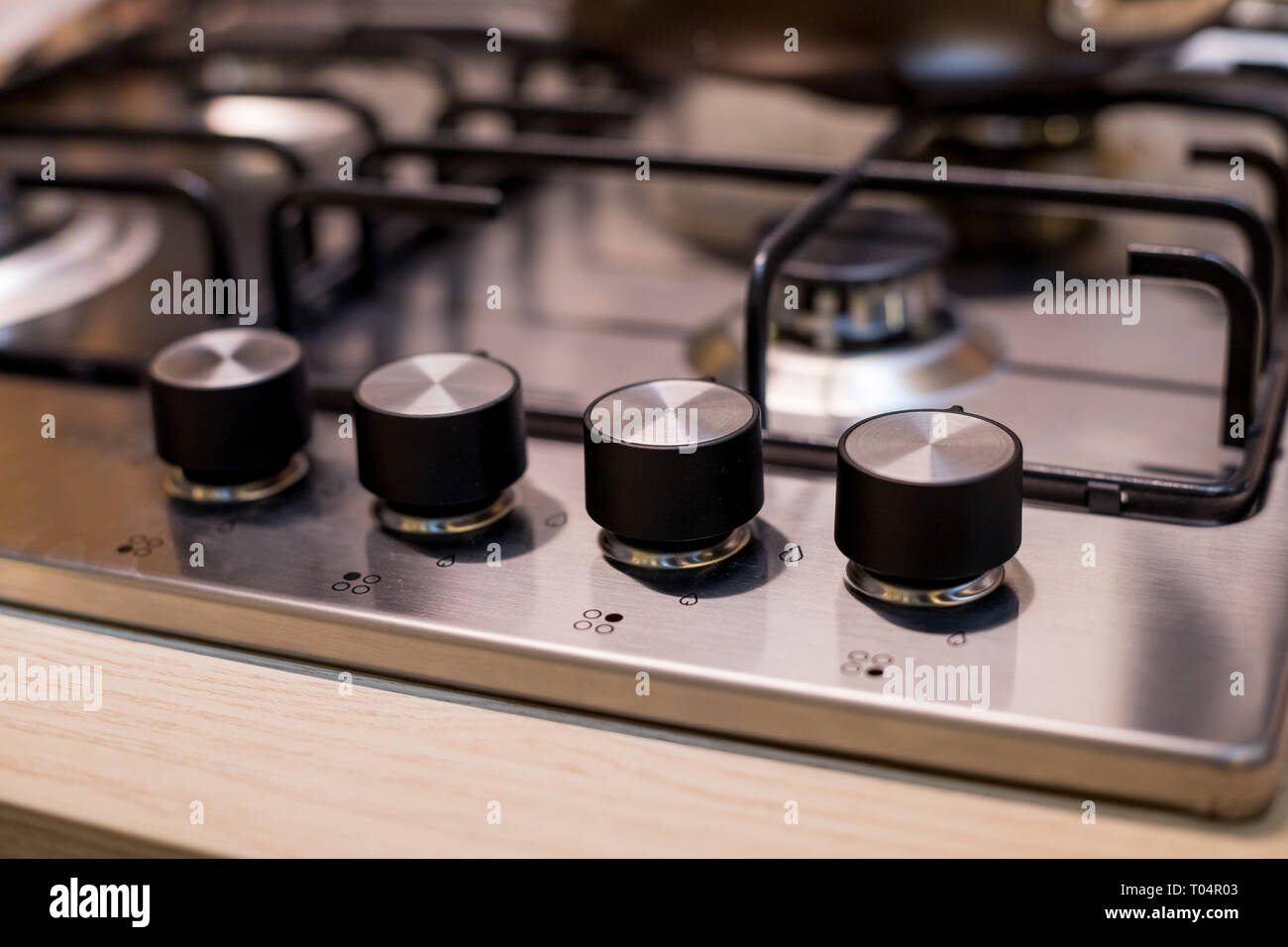 Metal gas stove on modern kitchen. the concept of forced savings on utilities Gas stove.knob heat switch ,elegant metal ,steel black and white.gas - Stock Image