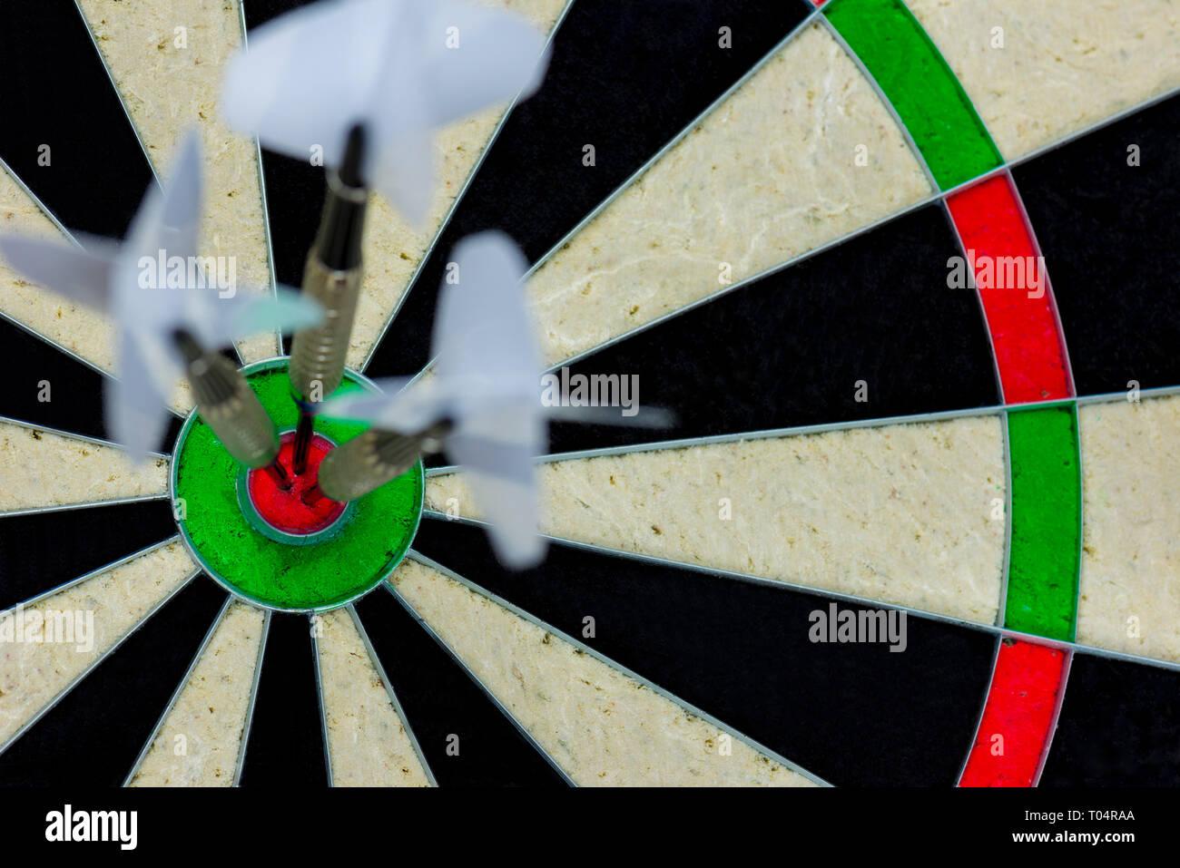 three darts thrown at the bulls eye of a dartboard - Stock Image