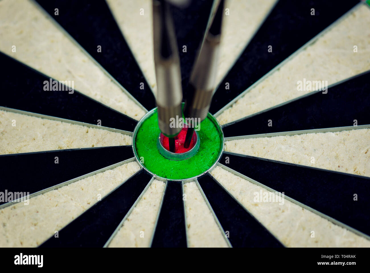 three darts thrown at the bulls eye of a dartboard Stock Photo