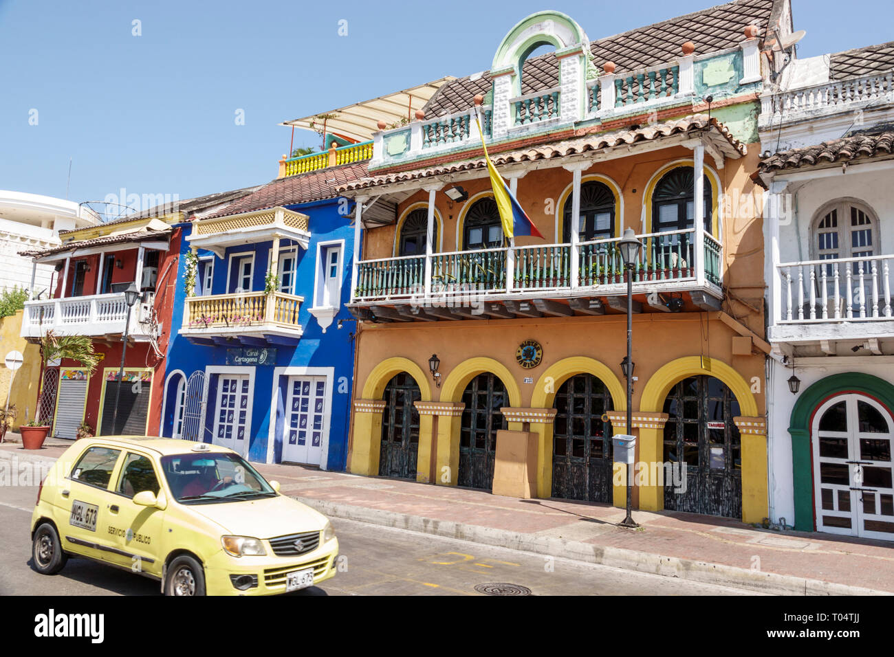 Cartagena Colombia Old Walled City Center centre Getsemani taxi taxis cab cabs historic colorful buildings facade front - Stock Image