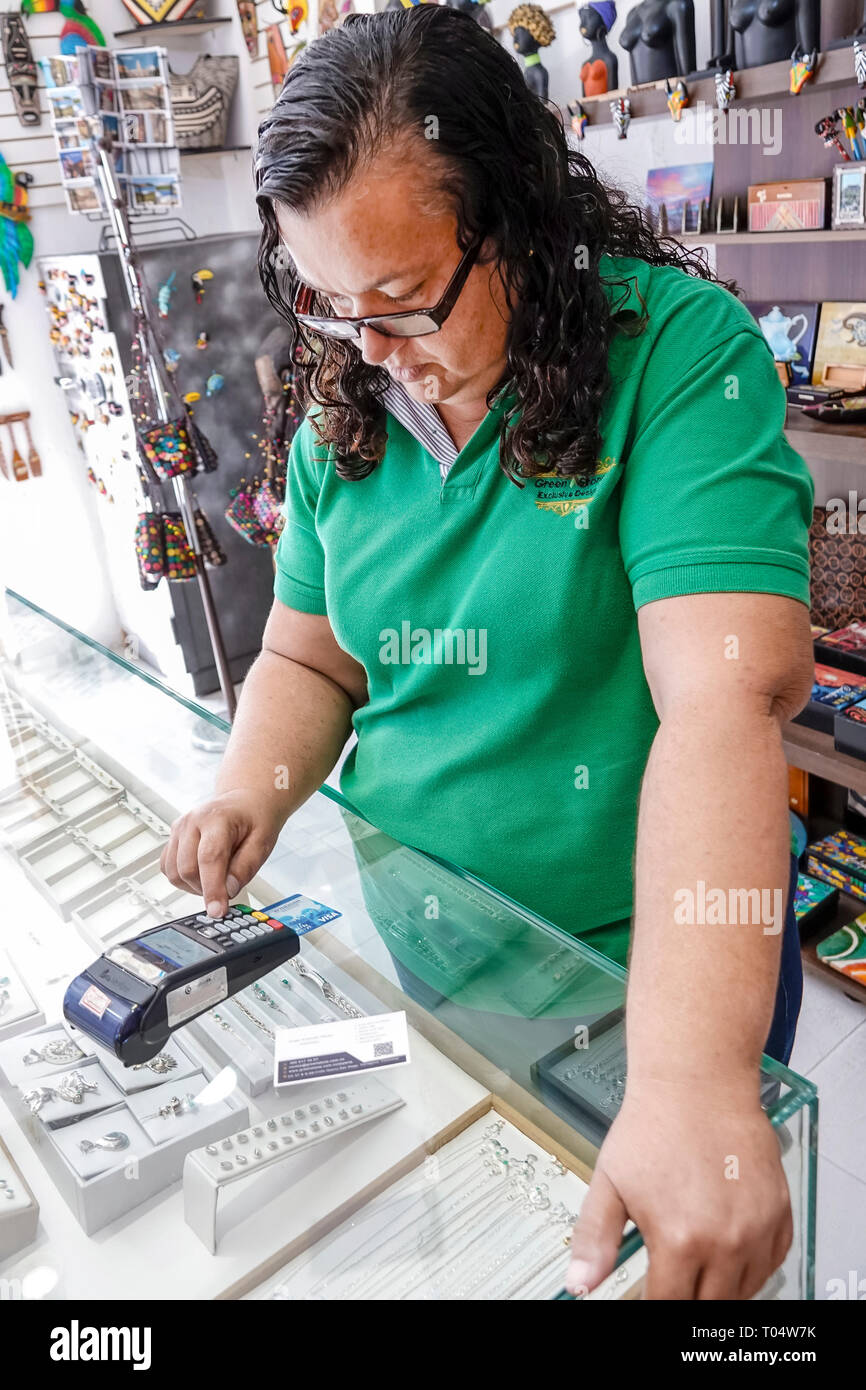 Cartagena Colombia Old Walled City Center centre San Diego Hispanic woman jeweler jewelry jewellery shop store small business manager owner using cred - Stock Image