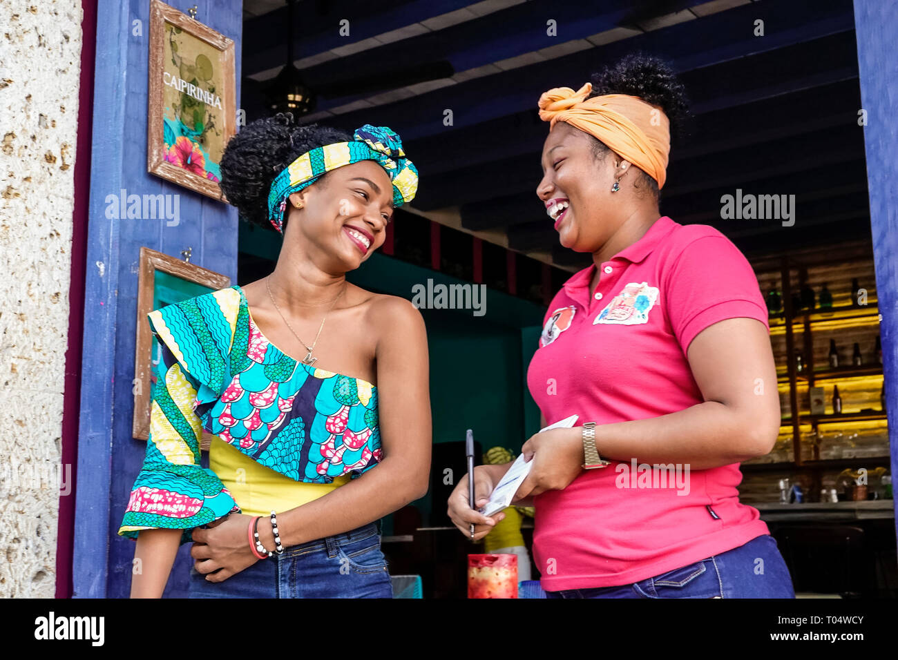 Cartagena Colombia Old Walled City Center centre Getsemani Hispanic resident residents woman restaurant bar hostess waitress co-workers typical turban - Stock Image