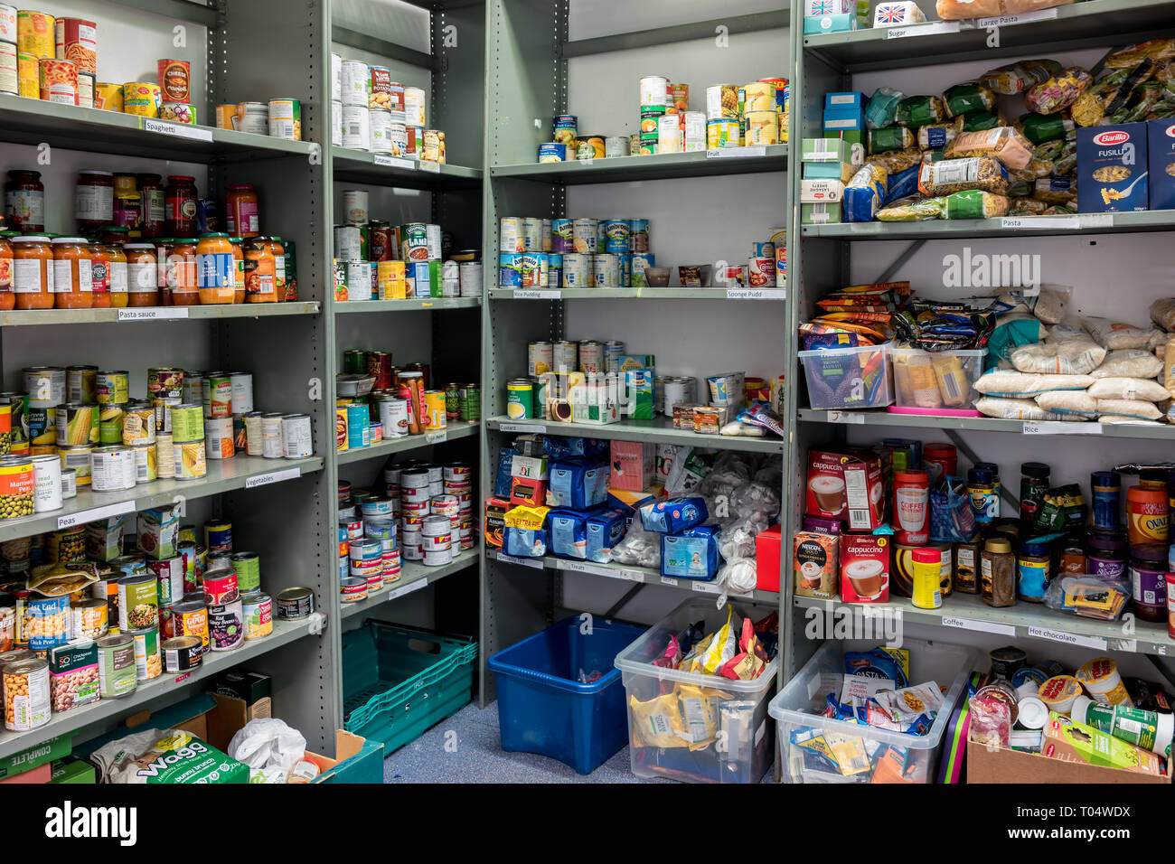 Storage shelves in a Trussell Trust local church food bank warehouse showing a variety of tins and store cupboard essentials ready for food parcels - Stock Image