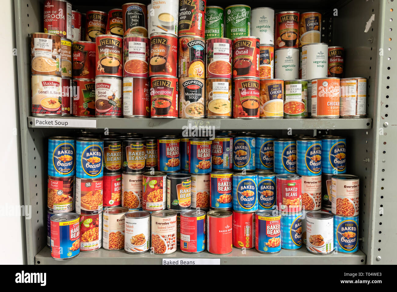 Storage shelves in a Trussell Trust local church food bank warehouse in the UK showing tins of baked beans and soup ready for food parcels - Stock Image