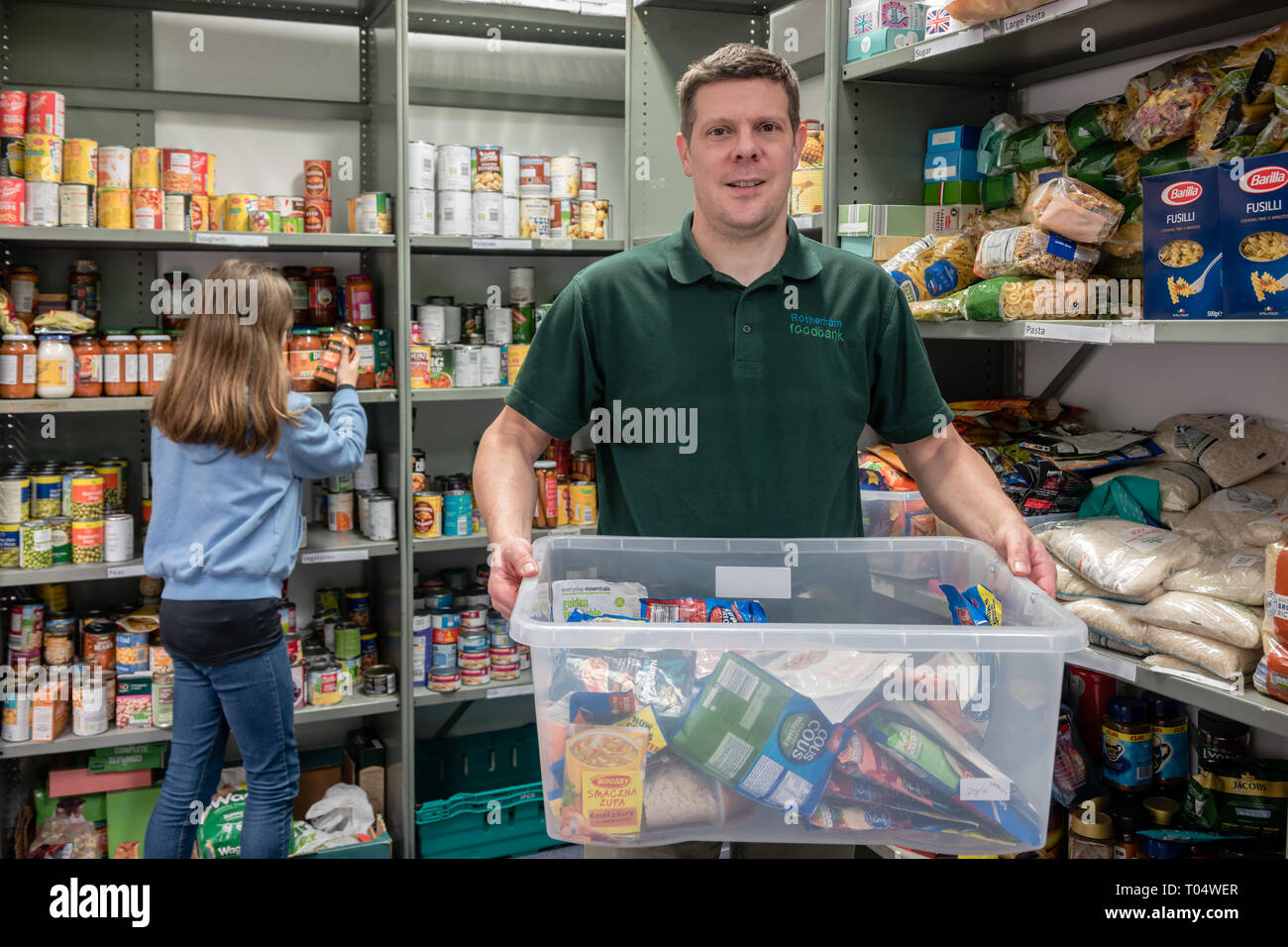 Volunteer workers in a UK Trussell Trust local church food bank packing shelves and holding donations - Stock Image