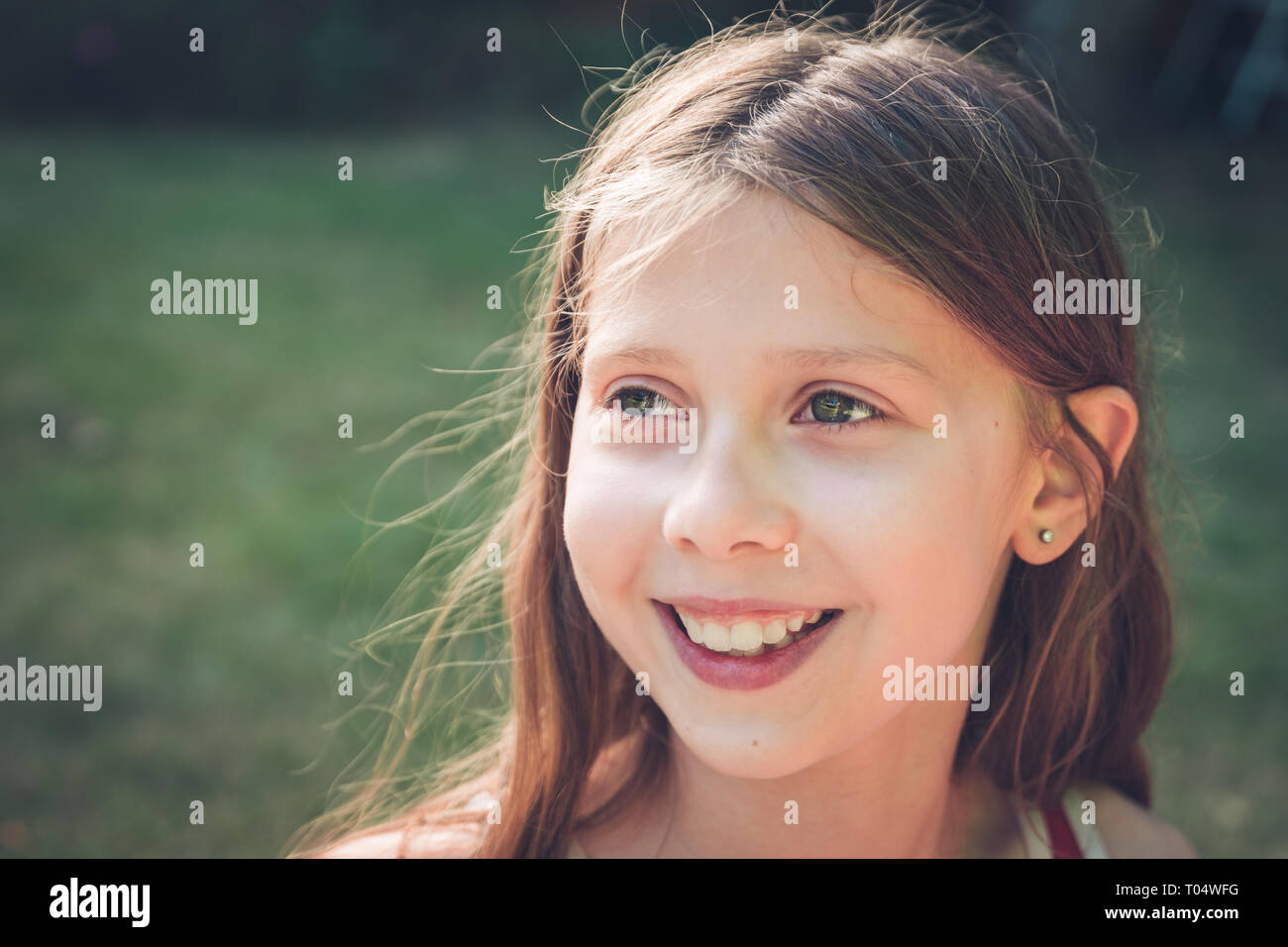Relaxed outdoor portrait of white girl child smiling and looking happy, gazing to the side - Stock Image