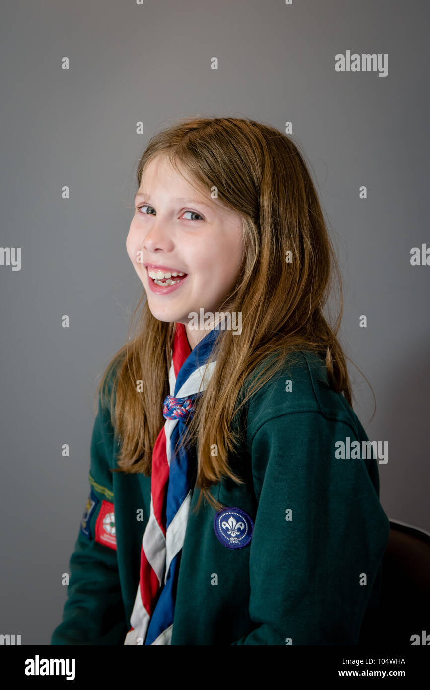 A portrait photo of a laughing British girl female cub scout in uniform with green sweatshirt, red, white and blue neckerchief and slider or woggle - Stock Image