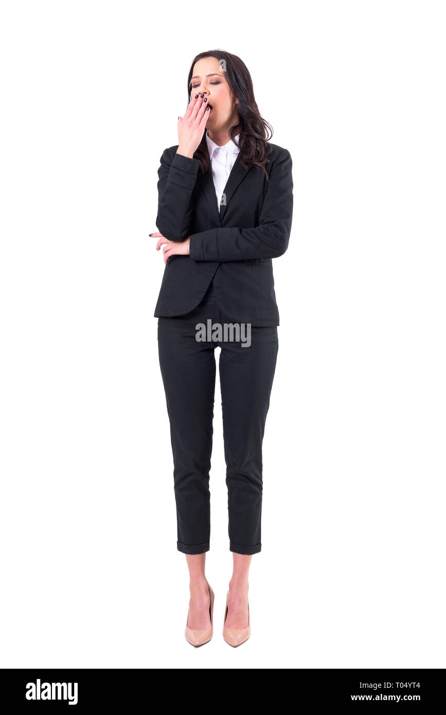 Tired sleepy overworked business woman in black suit yawning with closed eyes. Full body isolated on white background. - Stock Image