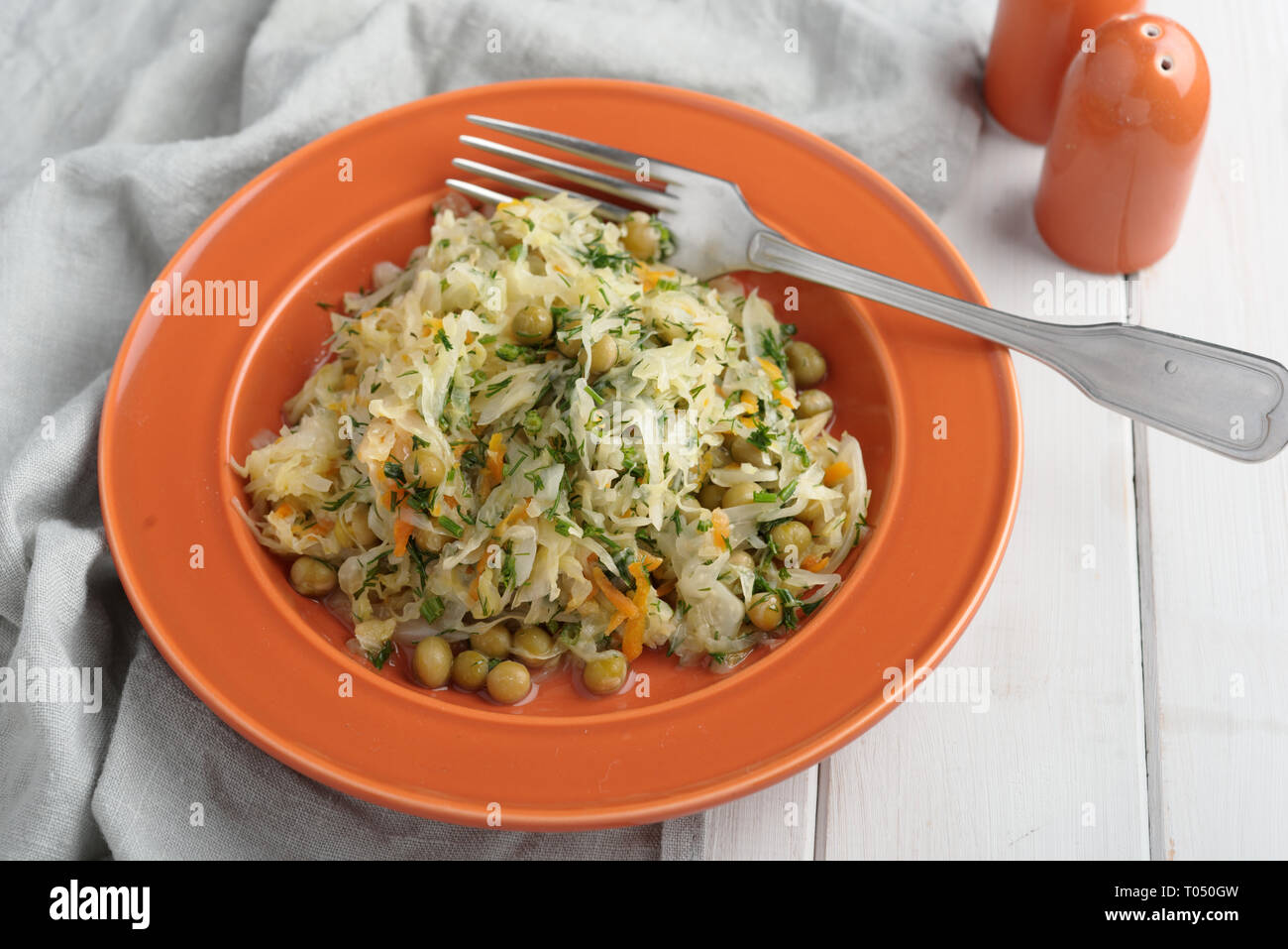 Braised cabbage with green pea, carrot, onion, and dill - Stock Image
