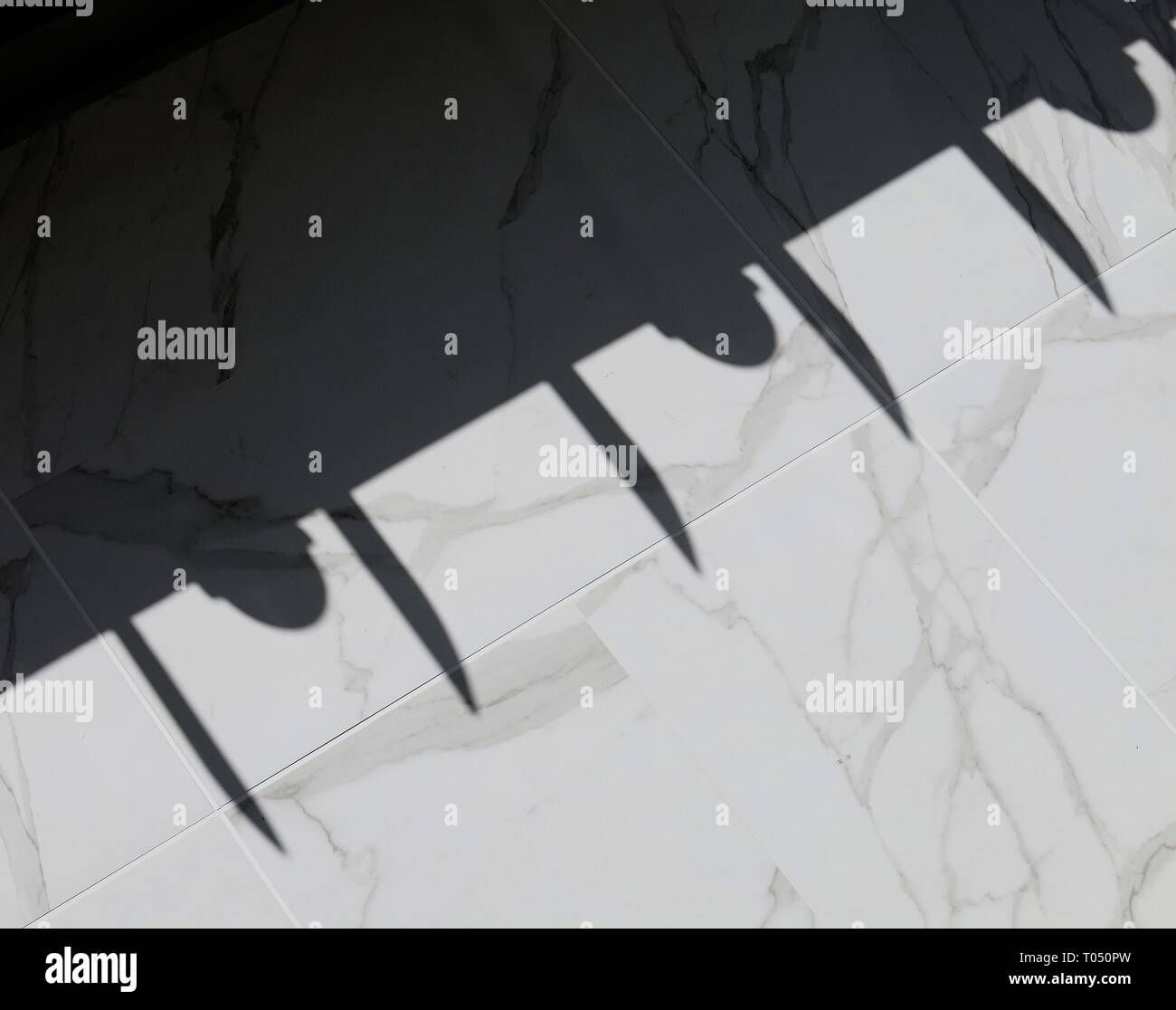 Shadows cast on tiled wall. - Stock Image