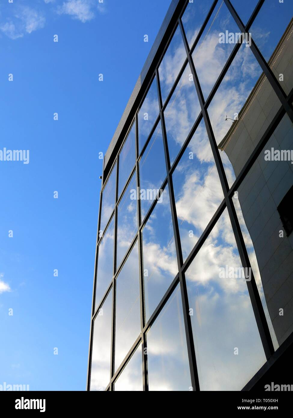 Reflection of clouds on window panes of a building. - Stock Image
