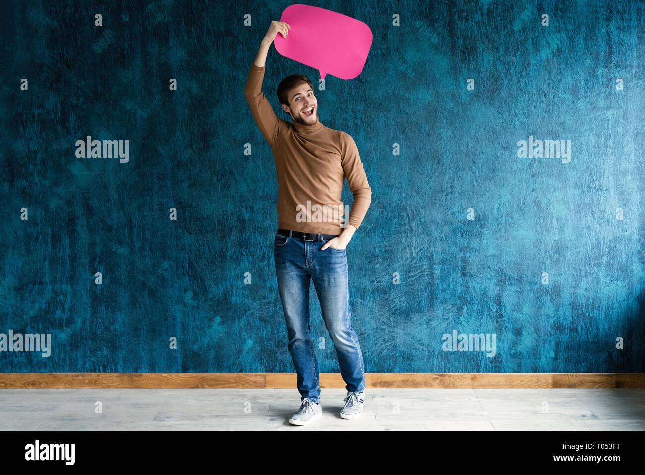 Let's start a conversation. I speak the language of success. Handsome young man holding up speech bubble isolated on dark blue. - Stock Image