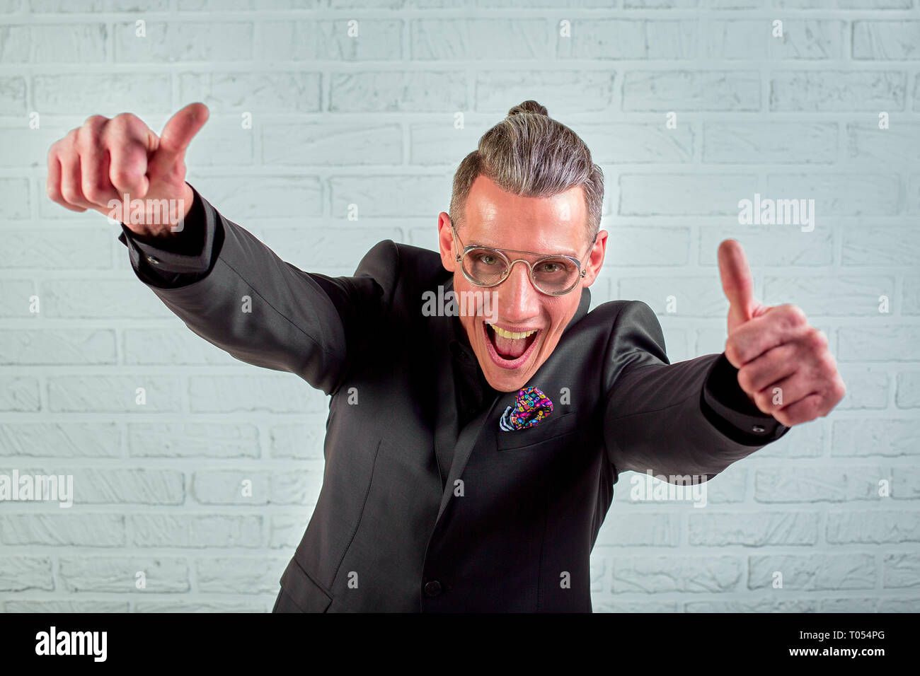 Positive businessman smiling looking at camera showing hand gesture thumbs up sign symbol - Stock Image