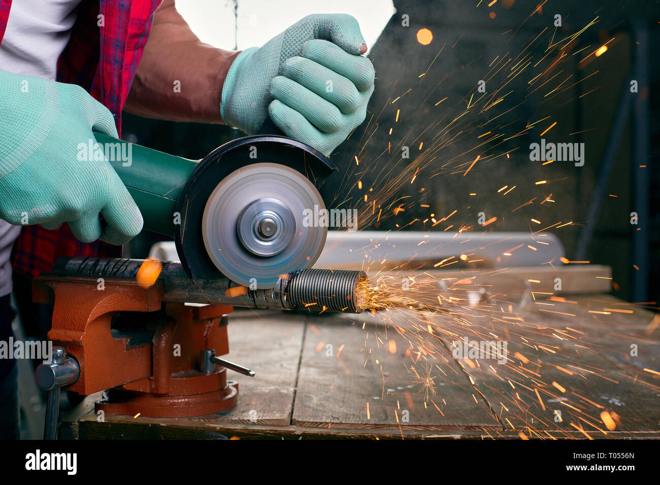Gloved hands hold an angle grinder and cut the pipe, many sparks fly to the sides - Stock Image