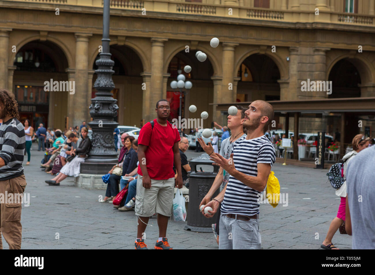 Street performers juggle balls for tourists at the Piazza della Repubblica, Florence, Tuscany, Italy. - Stock Image