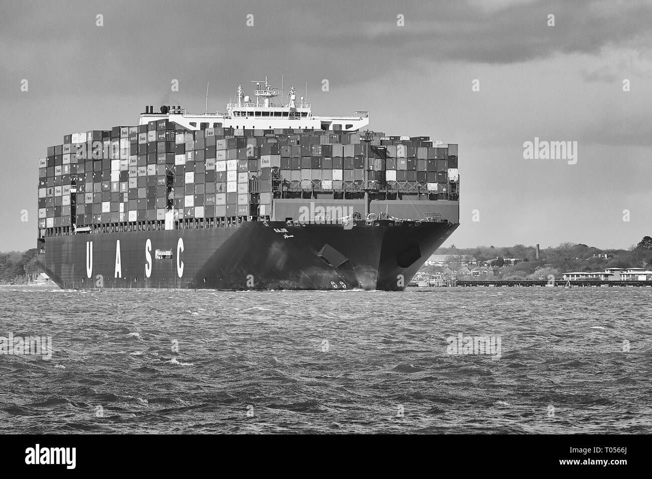 Black & White Image Of The Fully Loaded Ultra-Large UASC Container Ship, SAJIR, Departing The Port Of Southampton, Hampshire, United Kingdom. - Stock Image