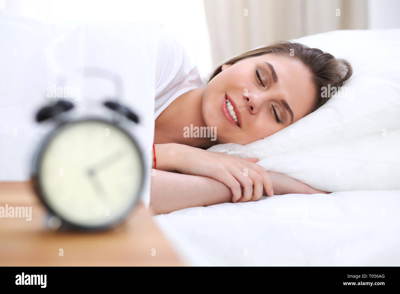Beautiful young and happy woman sleeping while lying in bed comfortably and blissfully smiling - Stock Image