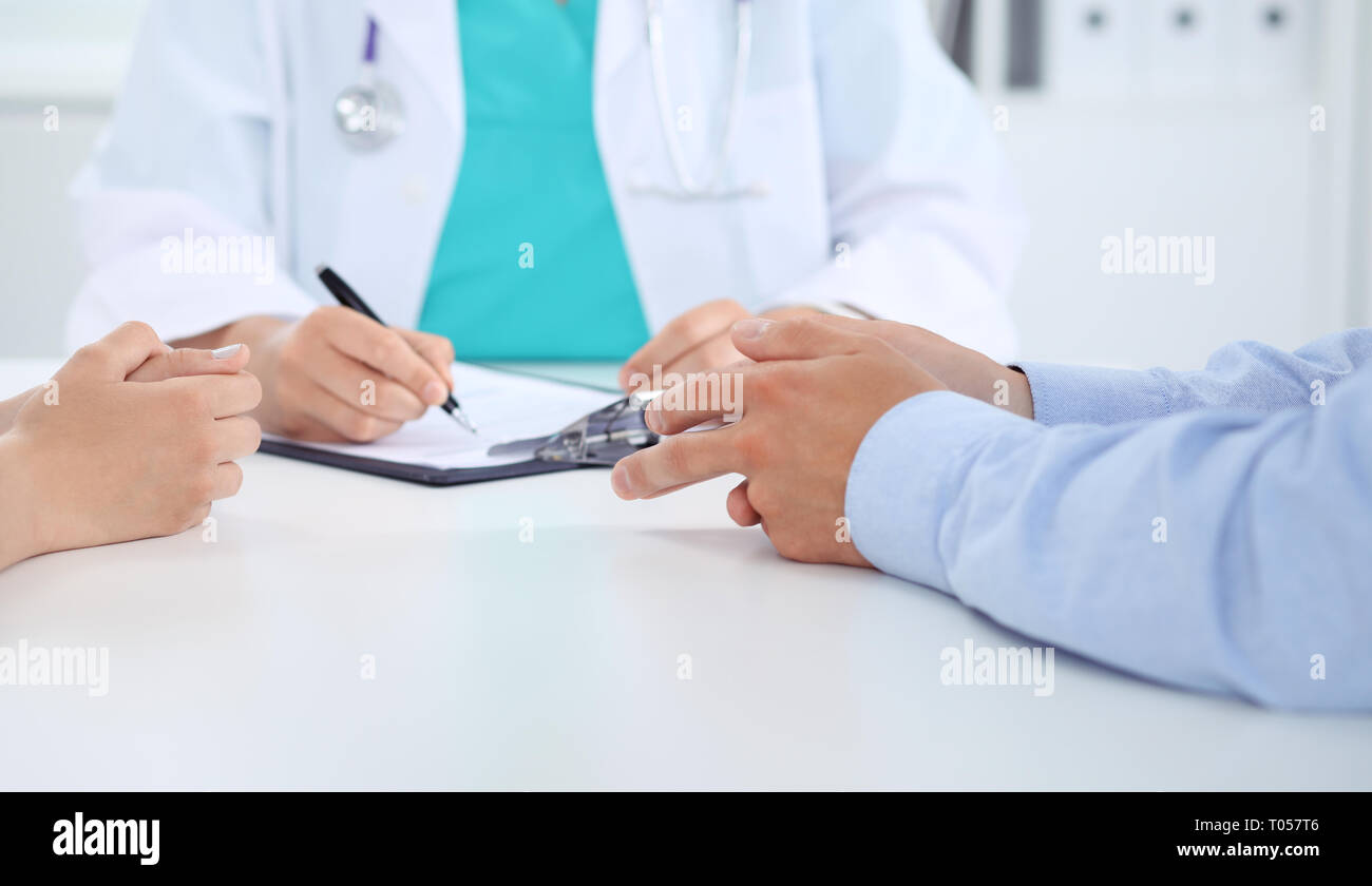 Doctor and patient couple are discussing something, just hands at the table - Stock Image