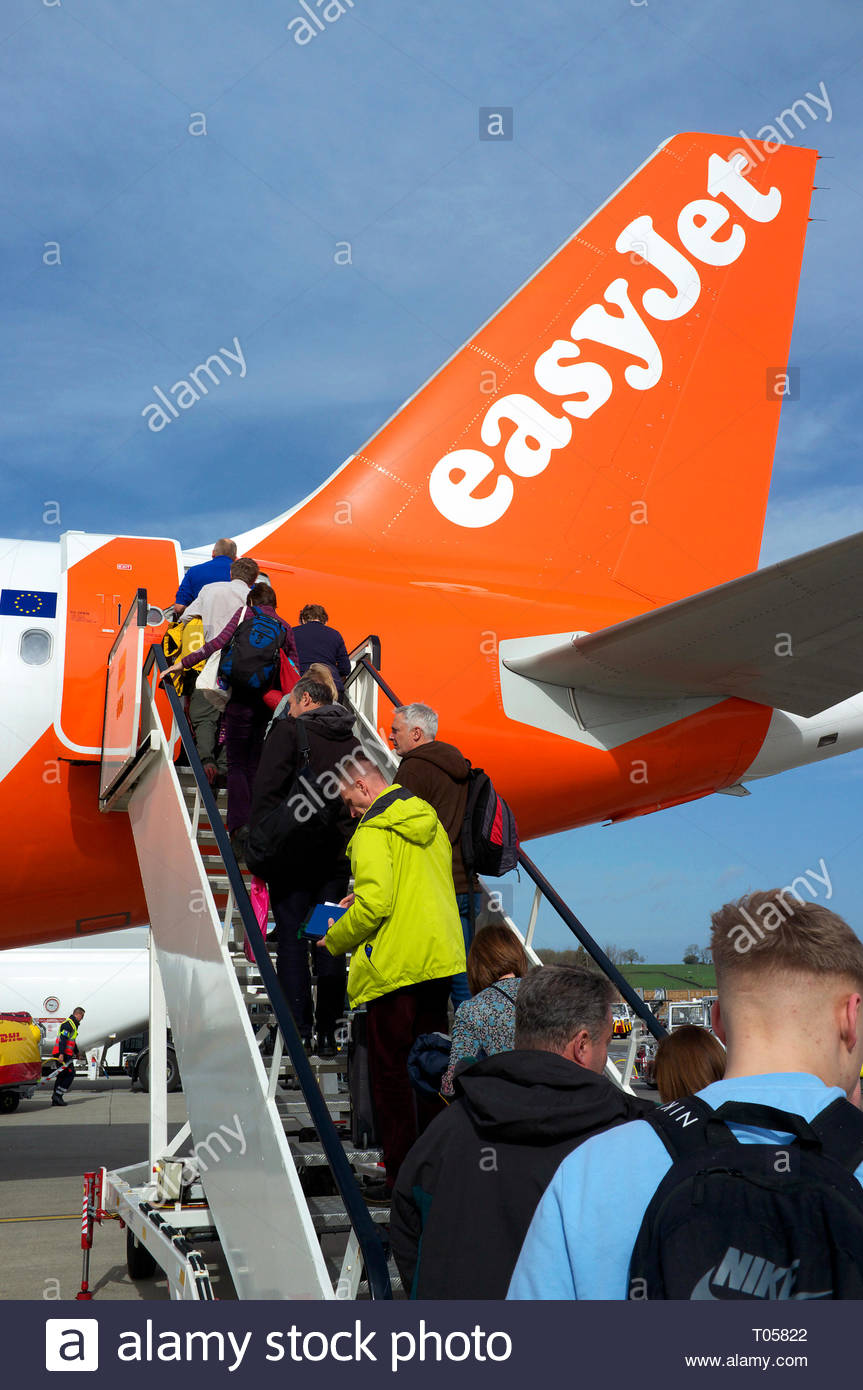 Passengers ascend the steps to board an Easyjet flight at Bristol Airport, Lulsgate, Bristol, UK. Stock Photo