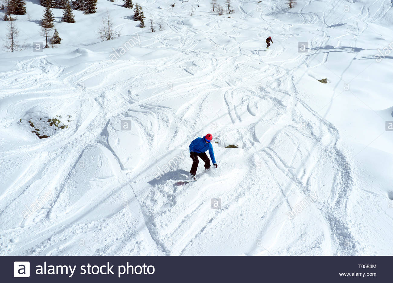 Two snowboarders go off piste, at the ski resort in Sainte-Foy-Tarentaise, Auvergne-Rhône-Alpes region in south-eastern France. Stock Photo
