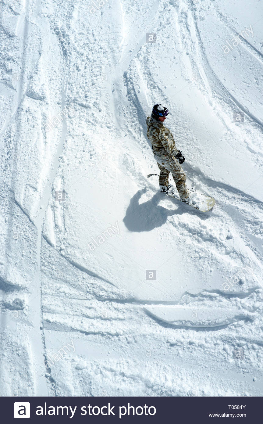 A snowboarder seen from above, off piste, at the ski resort in Sainte-Foy-Tarentaise, Auvergne-Rhône-Alpes region in south-eastern France. Stock Photo