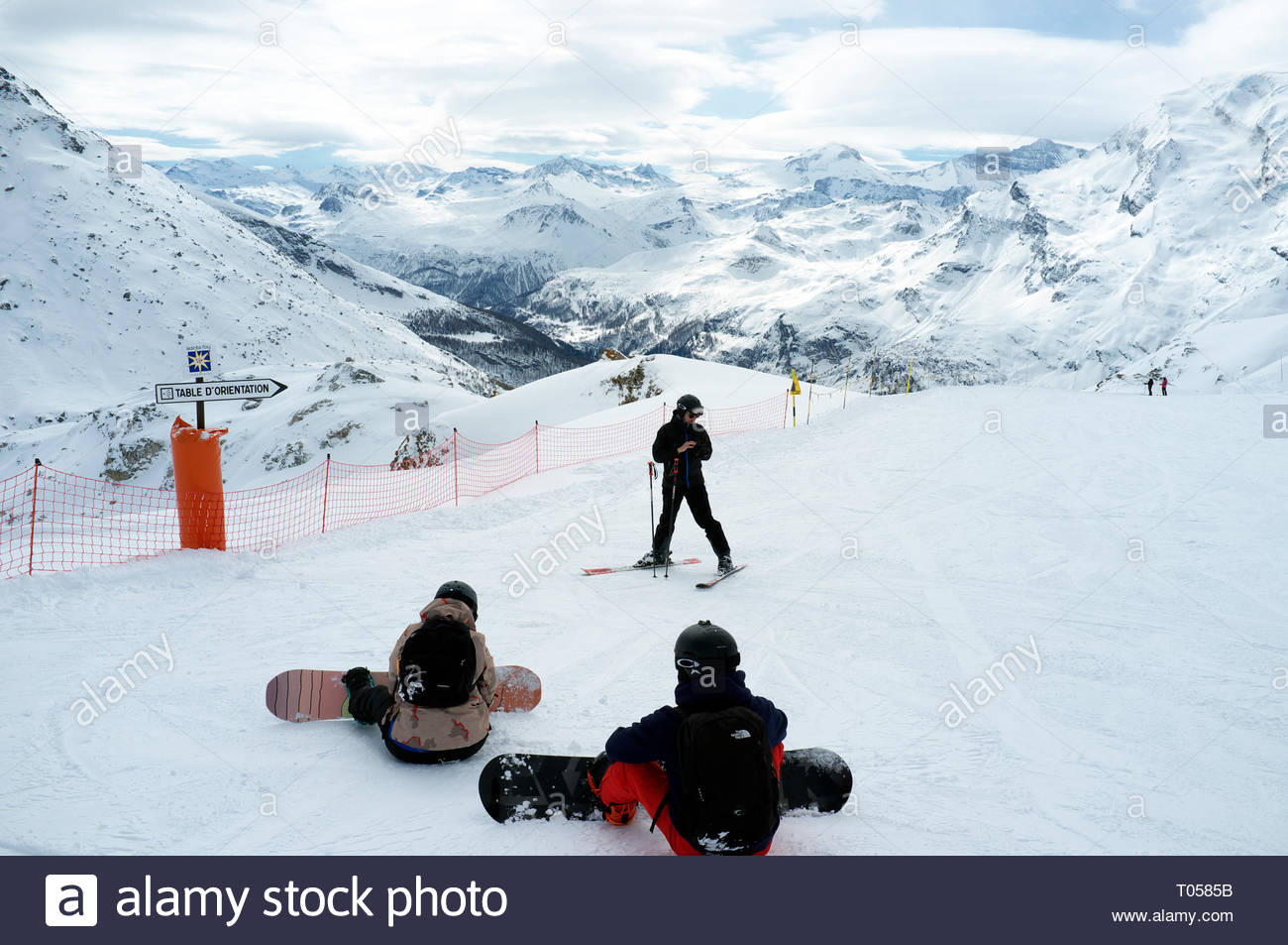 A skier and two snowboarders get ready to descend from the Sommet Aiguille, at the ski resort in Sainte-Foy-Tarentaise, Auvergne-Rhône-Alpes region in Stock Photo