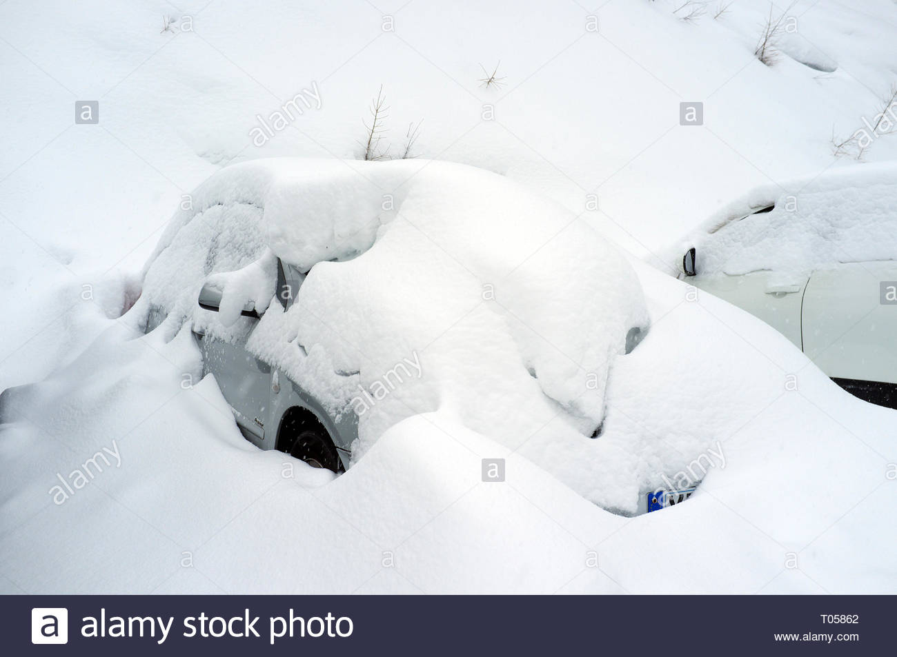 A parked car covered in snow, at the ski resort in Sainte-Foy-Tarentaise, Auvergne-Rhône-Alpes region in south-eastern France. - Stock Image