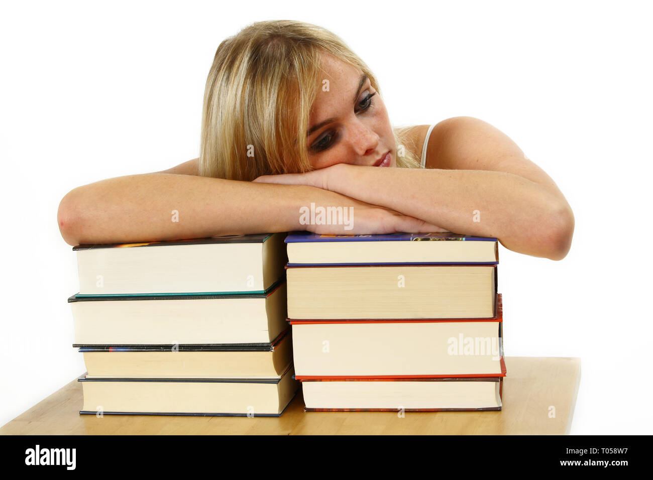 A young woman is leaning exhausted on a pile of books. Isolated against a white background. - Stock Image
