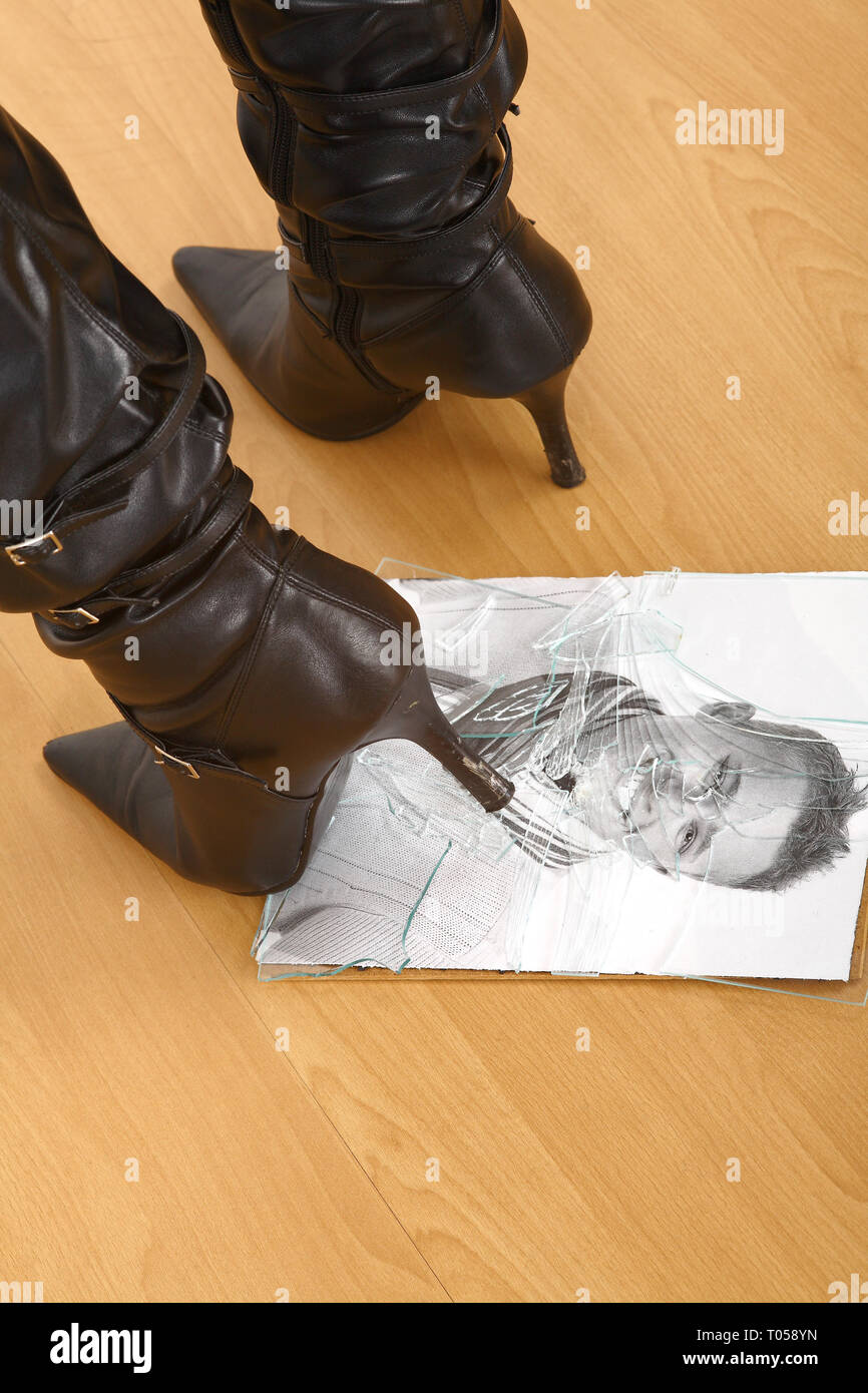 A young woman crushes a photo of her partner with her heel. The glass of the picture frame is shattered. - Stock Image