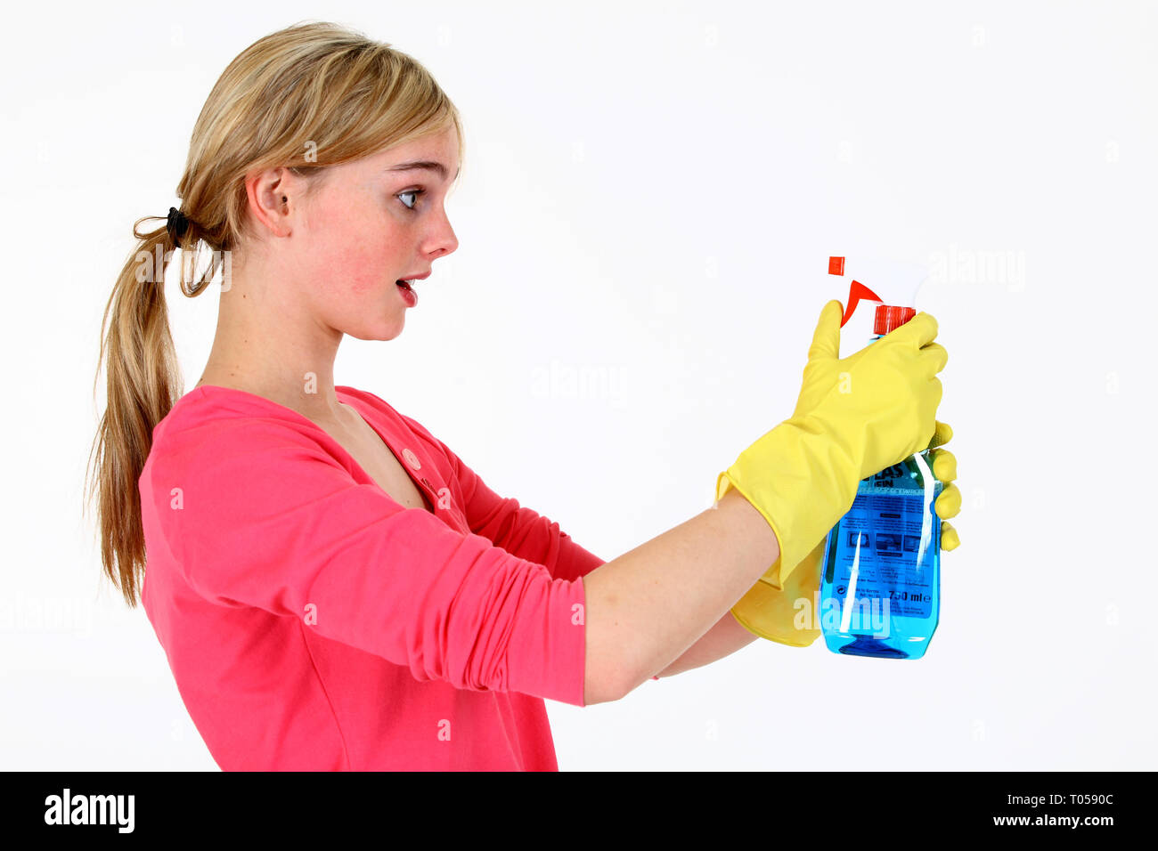 A young woman stares astonished at a spray bottle with cleaner. - Stock Image