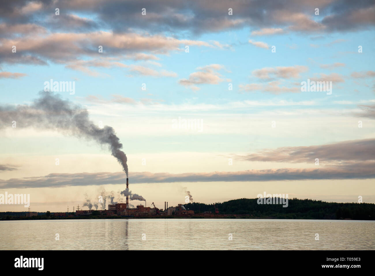 Smoking pipes of Pulp-and-paper factory on a lake in Russia - Carbon Dioxide emissions water pollution environmental issues concept - Stock Image