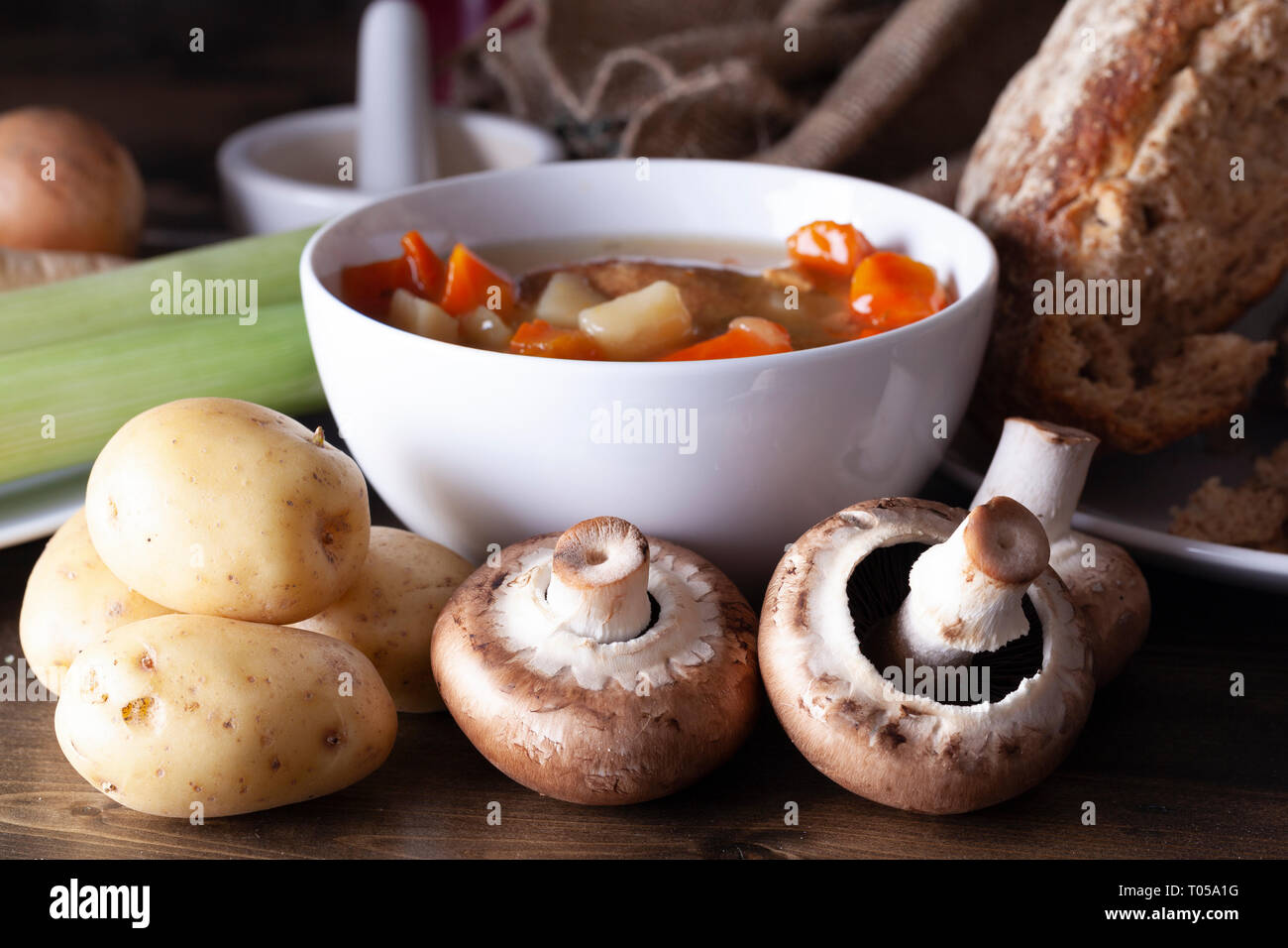 Winter food ona table with soup and brown mushrooms, potatoes and rustic bread. White bowl with warm brown tones Stock Photo