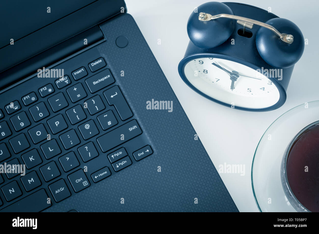 a work desk with a computer and office accessories and an alarm clock measuring the time running away. The concept of urgent deadlines at work - Stock Image