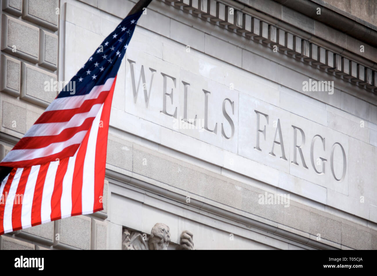 An America flag hangs above the entrance of a Wells Fargo branch in Center City Philadelphia, PA on March 15, 2019. - Stock Image