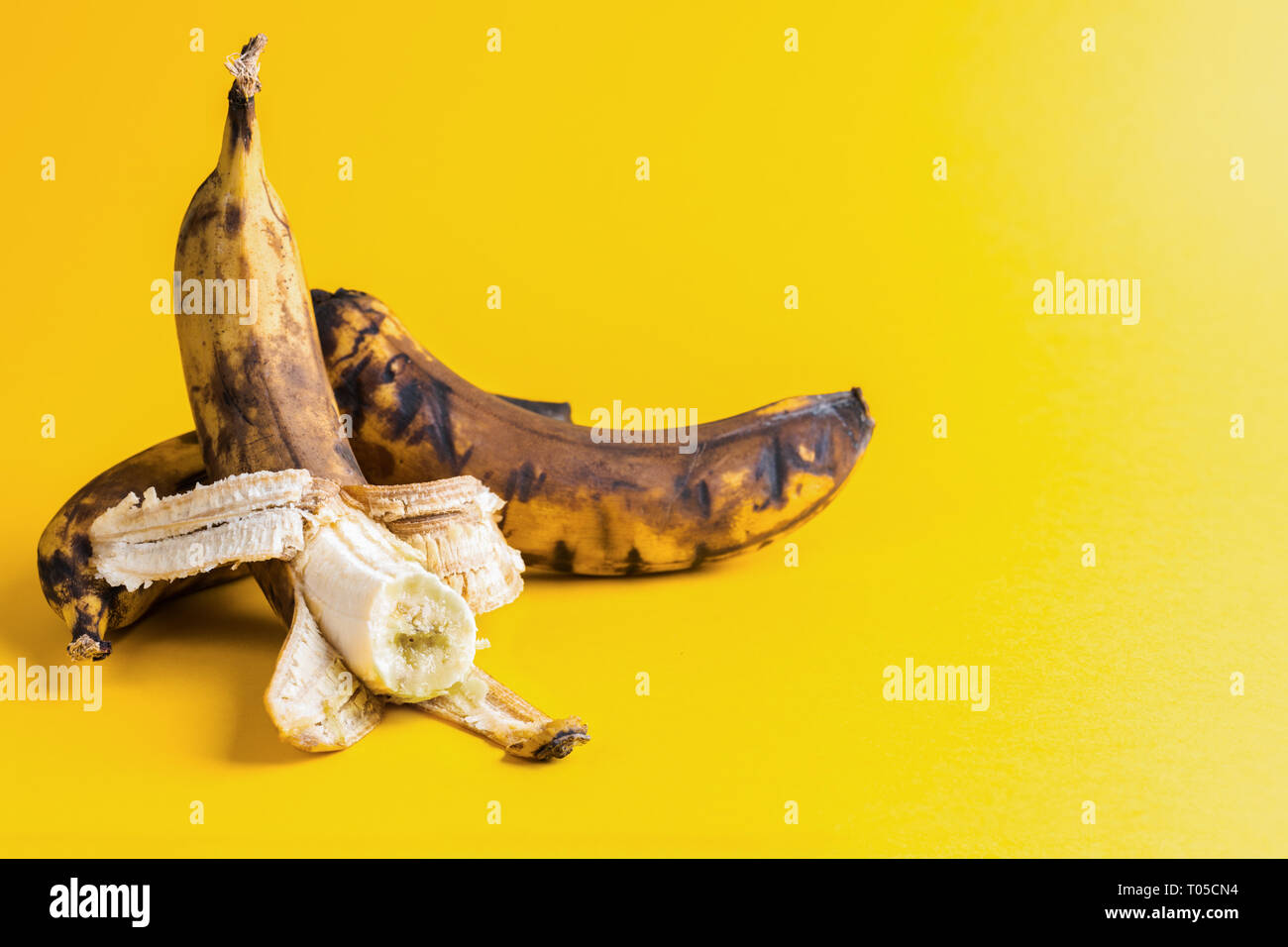 Two overripe blackened ugly bananas on bright yellow background . - Stock Image