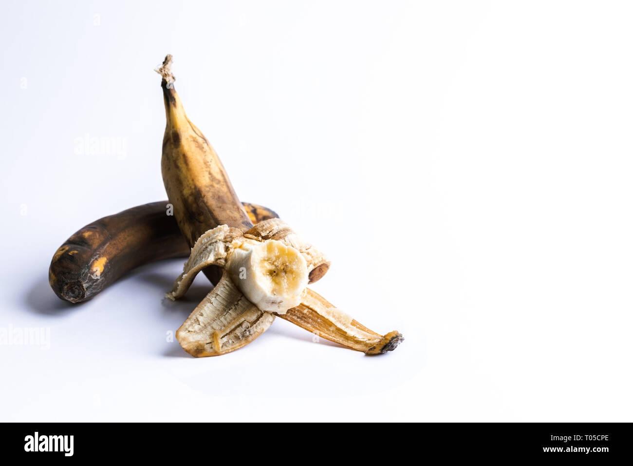 Two overripe blackened ugly bananas on white background. - Stock Image