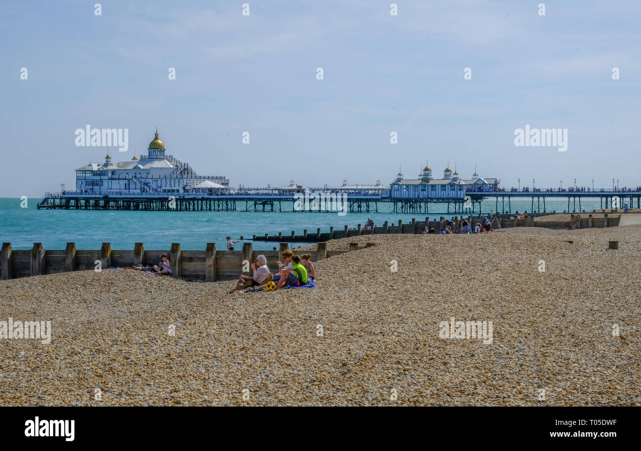 Eastbourne, Sussex, England, UK - August 1, 2018: View from the beach of the pier.  Family picnicing on the beach in the foreground.  Shot taken on a  Stock Photo