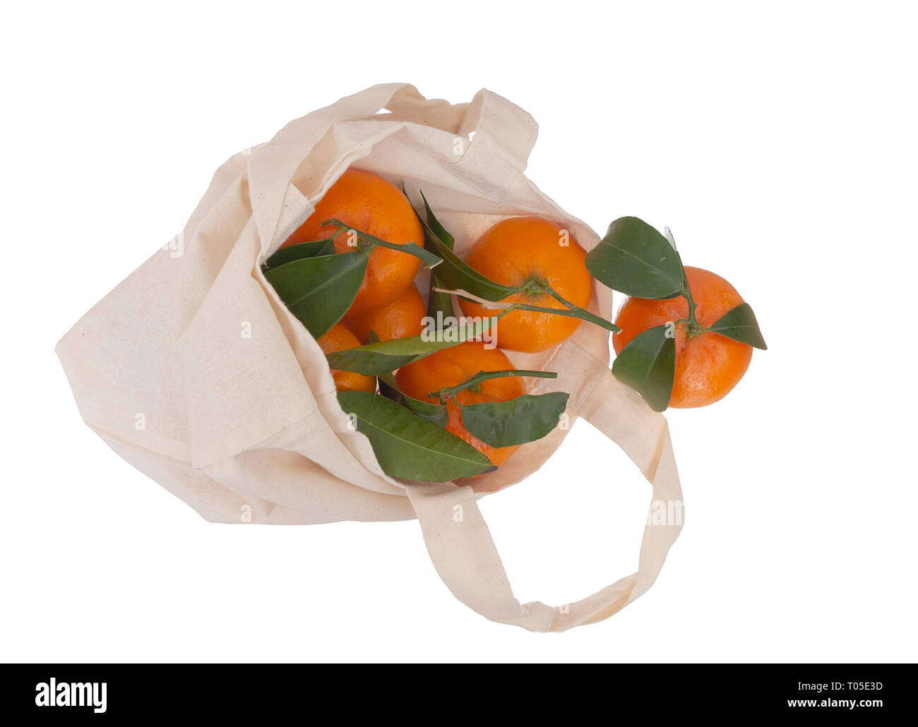 Fresh picked oranges in reusable, recyclable fabric shopping tote bag, isolated on white. For environmentally friendly, green consumers. - Stock Image